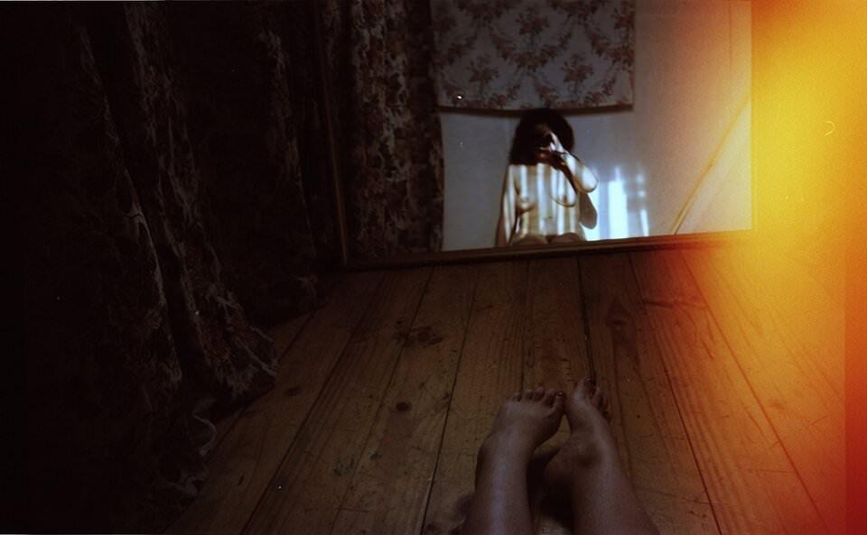 Frauen spiegelt sich oben ohne in einem Spiegel