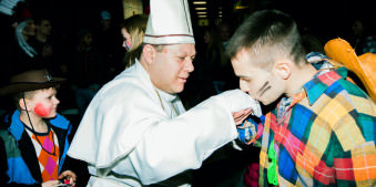 Karneval: Ein Cowboy küsst einem Papst die Hand.