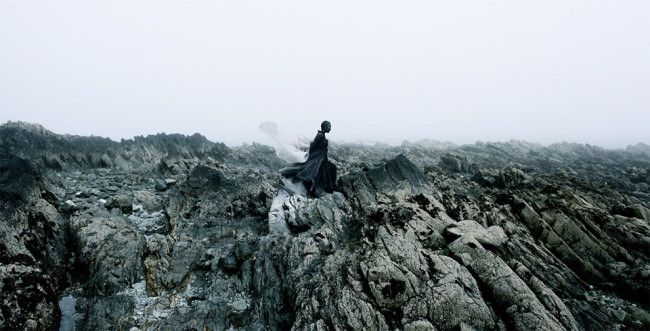 Eine Frau mit schwarz bemaltem Gesicht und schwarzer Kleidung geht über eine felsige Landschaft.