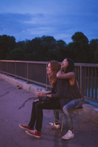 Zwei Mädchen albern in der Dämmerung herum und lachen.