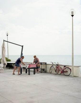 Ein paar spielt an einem Tischkicker vor einem Meer.
