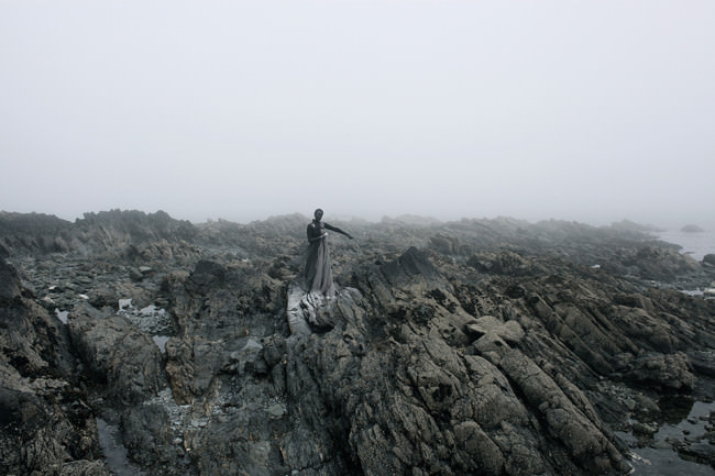 Eine Frau auf einem Felsen im schwarzen Kleid.
