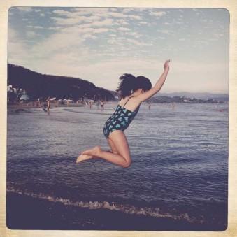 Ein Mädchen springt ins Meer.