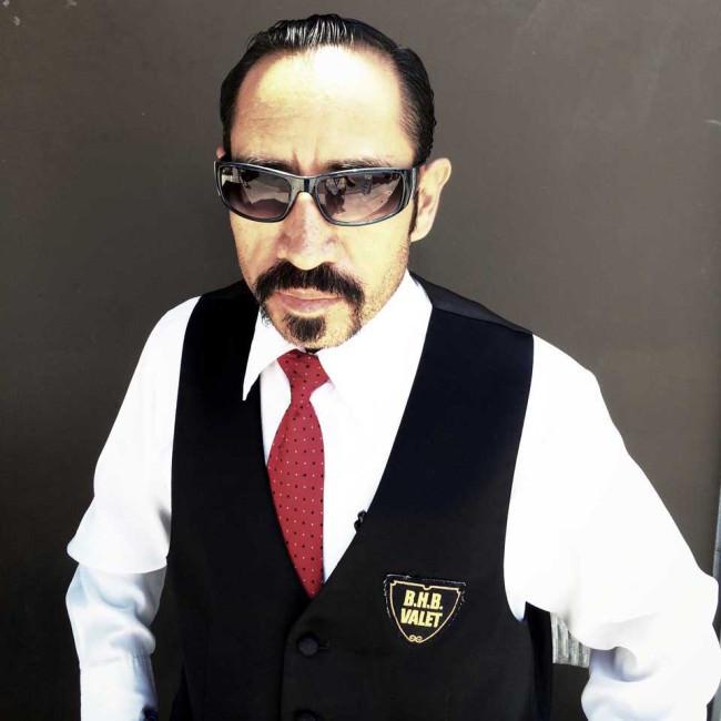 Ein Mann mit Sonnenbrille und roter Krawatte.