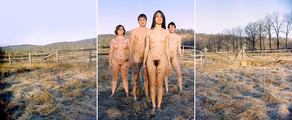 Vier nackte Menschen stehen auf einer Wiese.