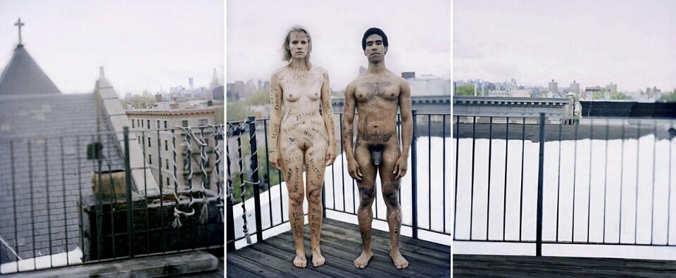 Zwei nackte und beschriftete Personen stehen auf einem Balkon.