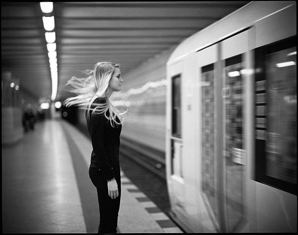 Eine Frau steht auf dem Bahnsteig und ihr Haar weht als der Zug an ihr vorbeifährt.