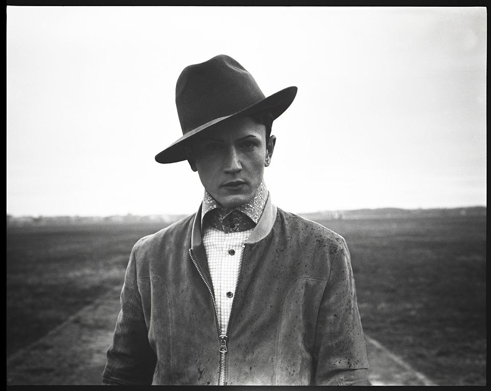 Ein Mann steht auf einem Feld mit einem Hut und schaut in die Kamera. Der Hut sitzt schief.