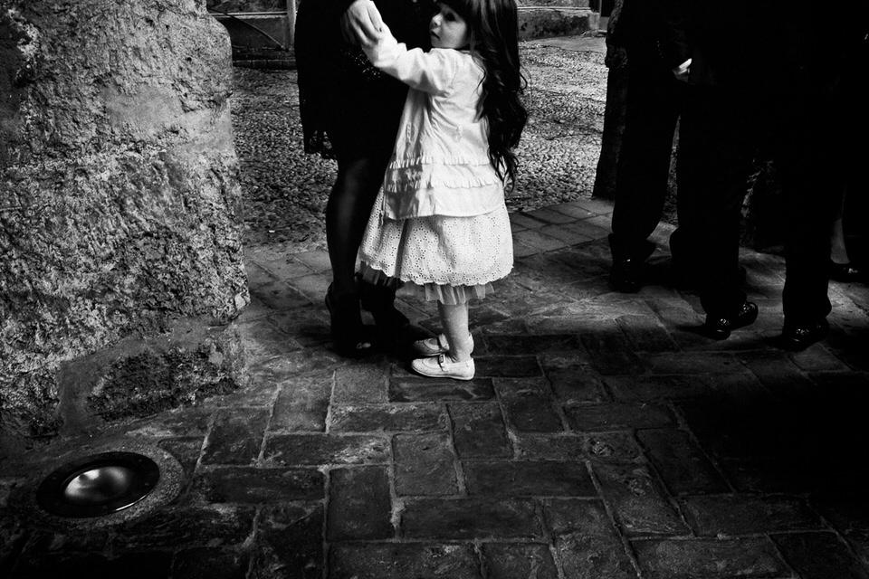 Ein Mädchen im weißen Kleid umklammert die Beine einer Erwachsenen.