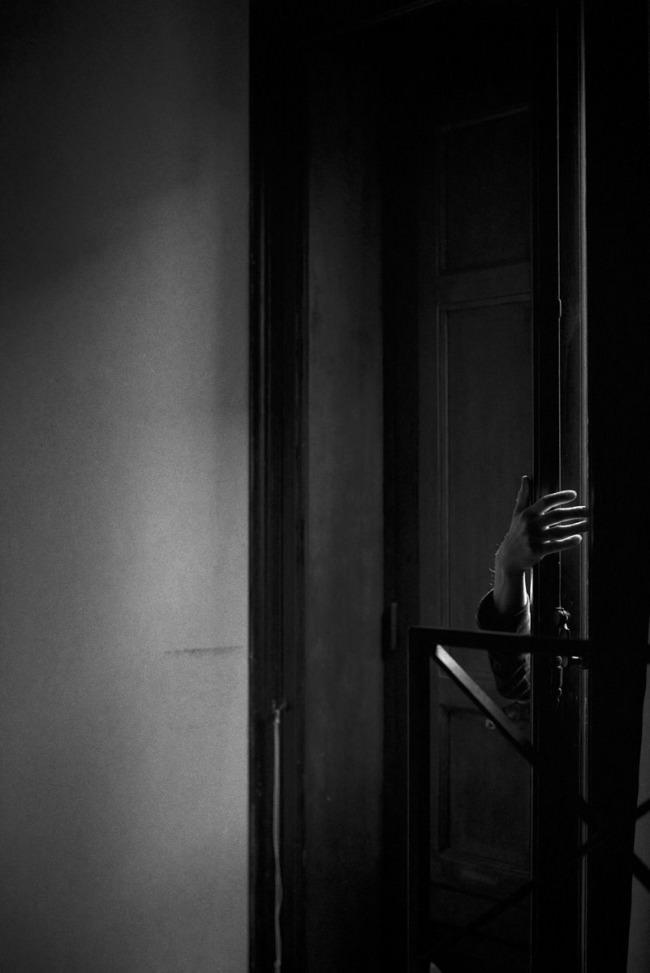 Eine Hand greift um die Türe.