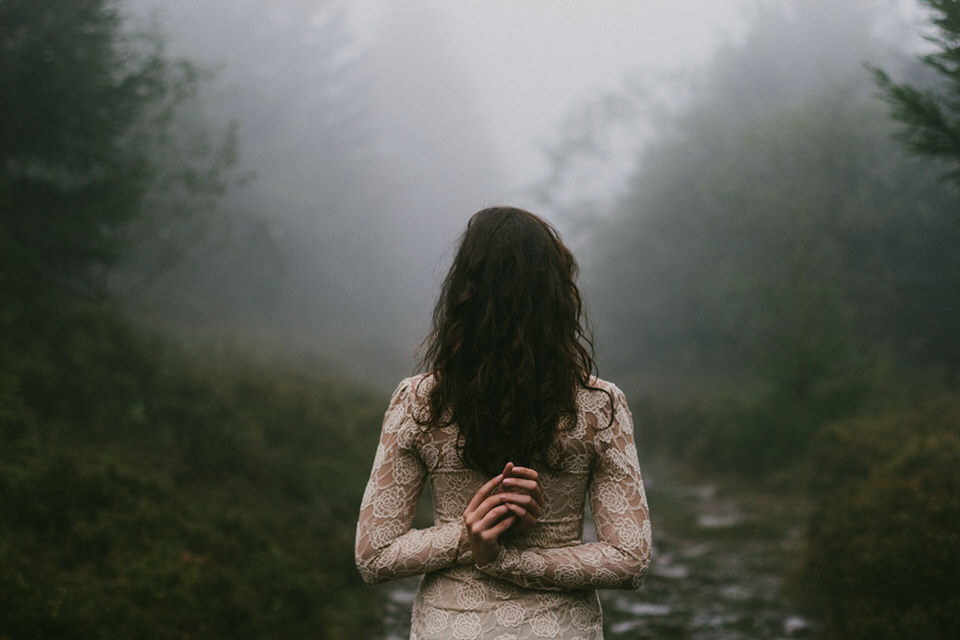 Eine Frau steht mit dem Rücken zur Kamera und sieht in den Nebel.