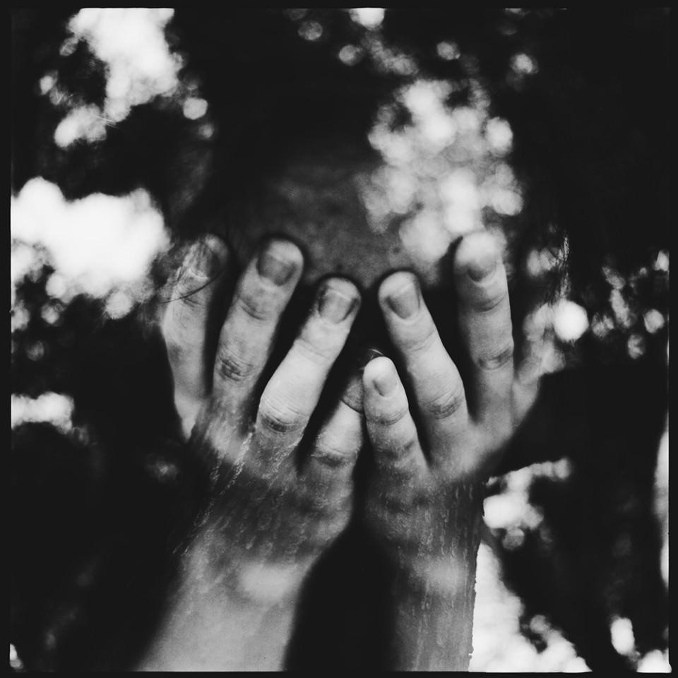 Doppelbelichtung eines Menschen mit Händen vor dem Gesicht und Lichtreflektionen