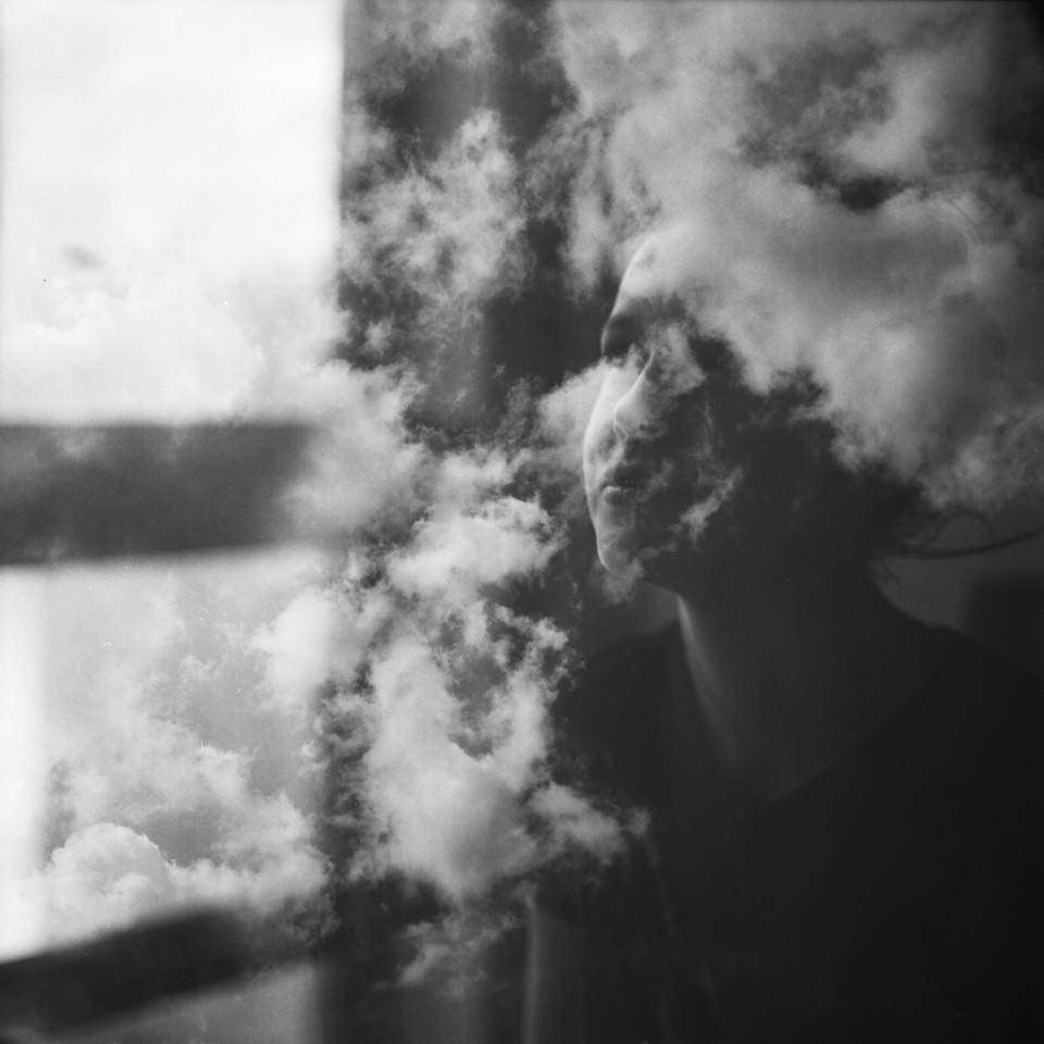Doppelbelichtung einer Frau und Wolken