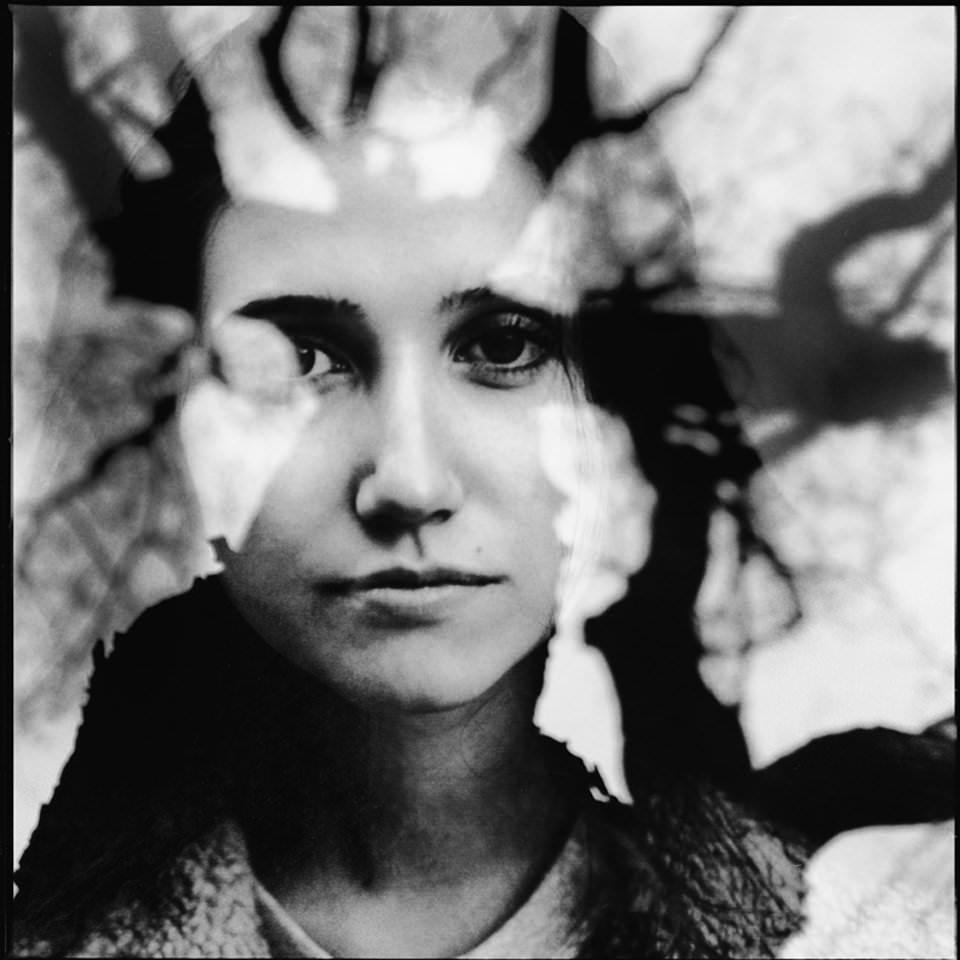 Doppelbelichtung einer Frau und einer Spiegelung eines Baumes