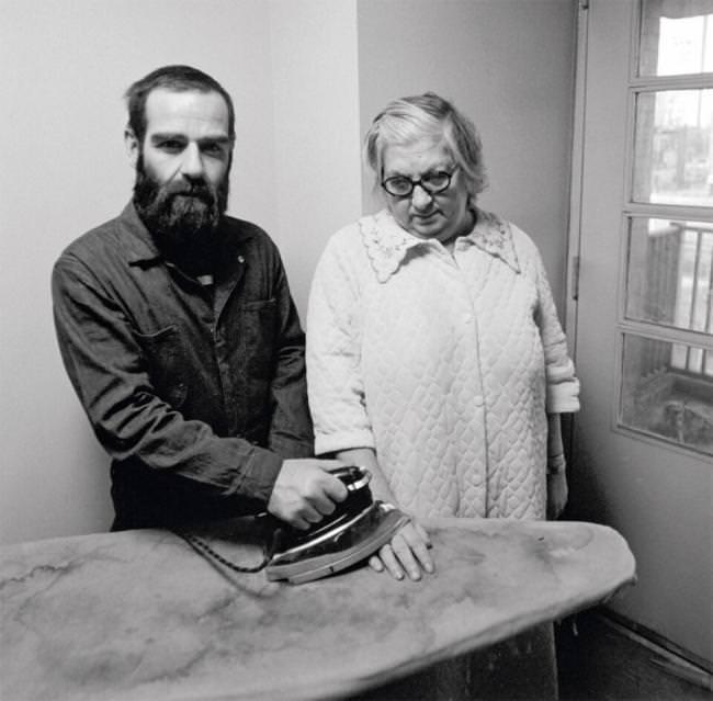 Ein Mann verbrennt seiner Frau die Hand mit einem Bügeleisen.
