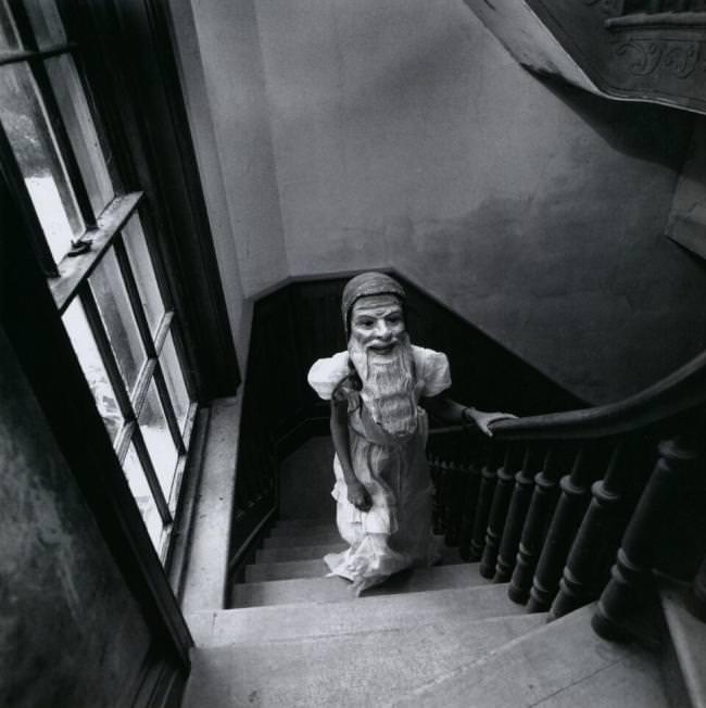 Ein riesiger Gartenzwerg läuft eine Treppe hoch.
