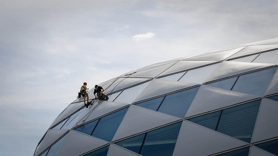 Zwei Reinigungsarbeiter putzen die Fassade eines postmodernen Gebäudes.