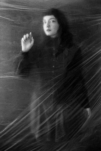 Eine Frau steht hinter einer Folienwand.