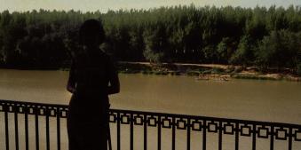 Eine Person steht vor einem Fluss