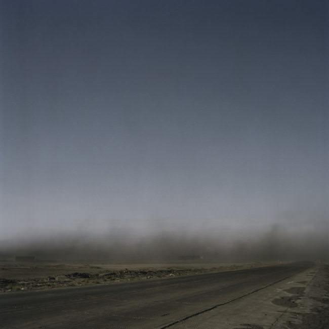Eine Kohlestaubwolke schwebt über einer Straße durch die mongolische Steppe.