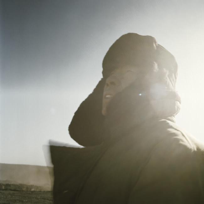 Ein chinesischer Bergarbeiter blickt in den sonnigen Himmel.