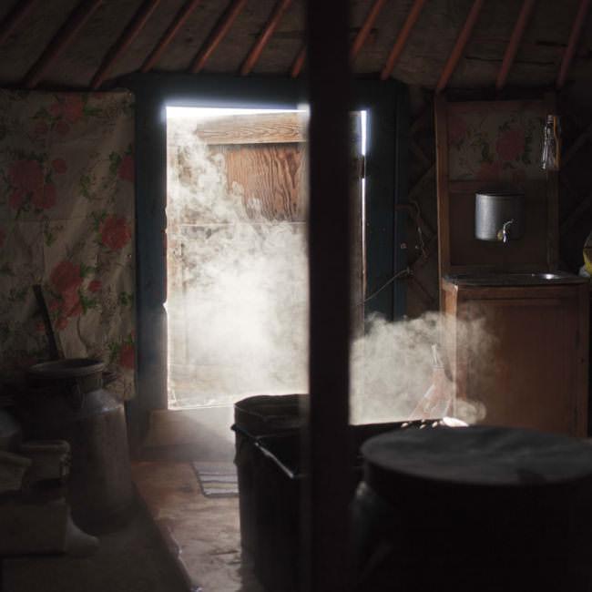 Wasserdampf steigt aus dem Kessel in einer Jurte auf.