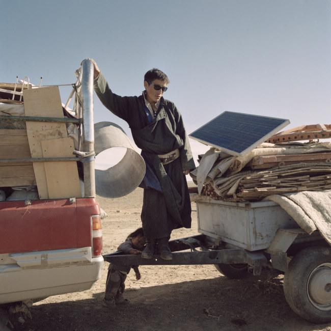Ein Mann steht auf einem voll beladenen Lastzug mit den Habseligkeiten der Nomdenfamilie.