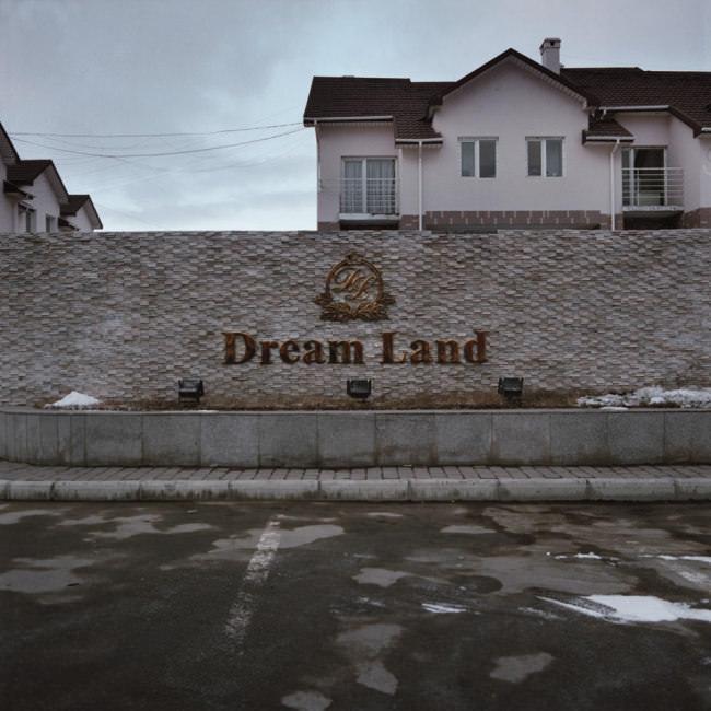 Ein Parkplatz vor einer Mauer mit der Aufschrift Dream Land.