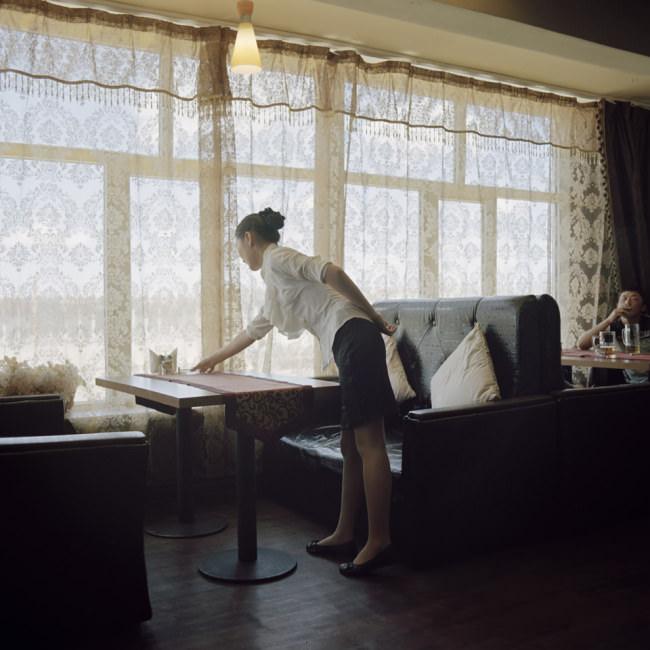 Eine Kellnerin deckt den Tisch in einem Restaurant.
