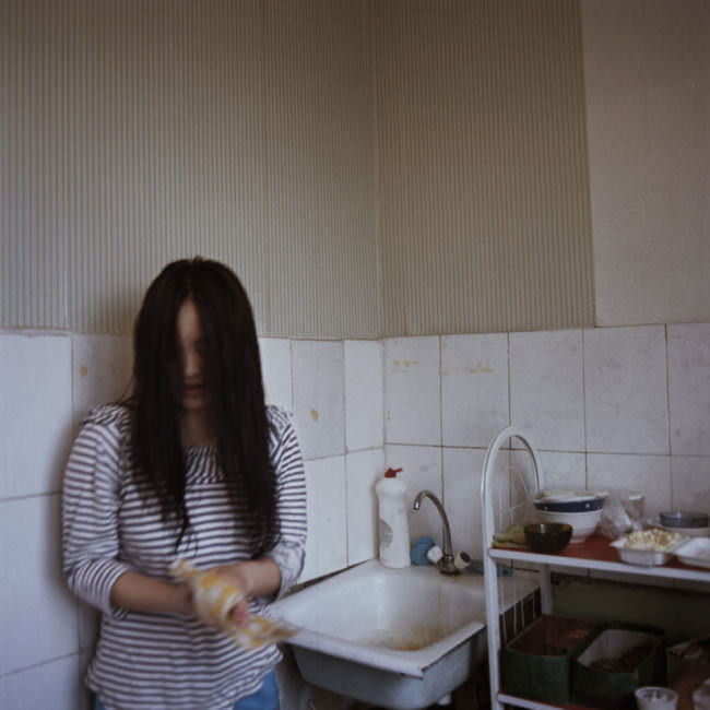 Eine junge Frau steht vor einem Spülbecken und trocknet sich die Hände ab.