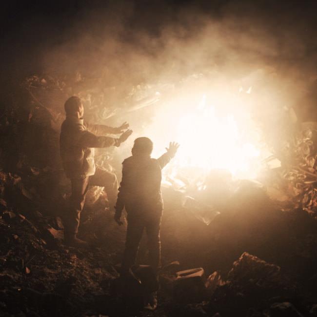 Zwei Männer stehen an einem Feuer auf einer Mülldeponie, wo sie nach Wiederverwendbarem suchen.