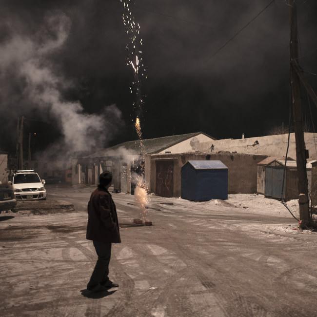 Ein Mann steht zu Silvester auf einer verschneiten Dorfstraße und zündet Feuerwerk.