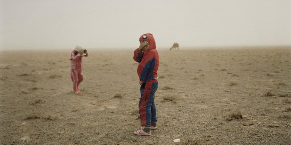 Zwei Kinder spielen draußen während eines Sandsturms.