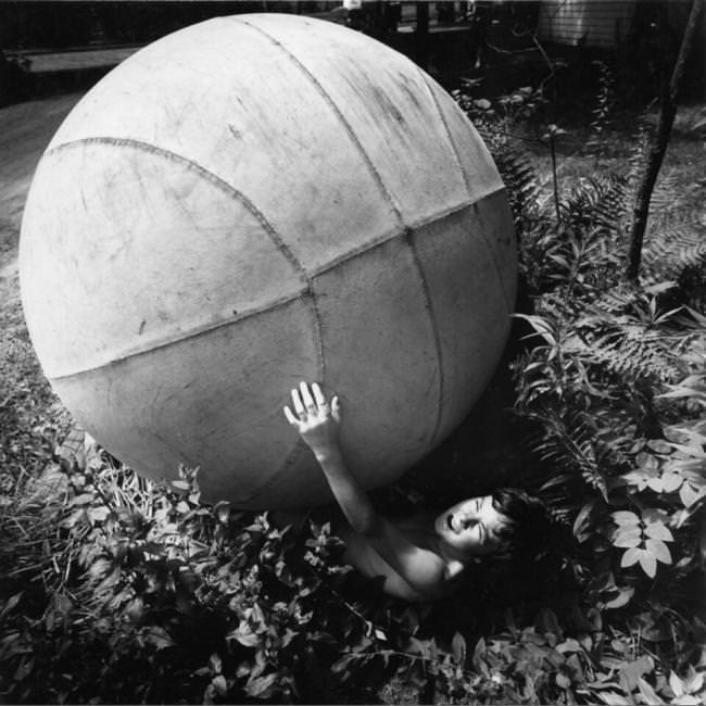 Ein riesiger Ball überrollt einen Jungen.