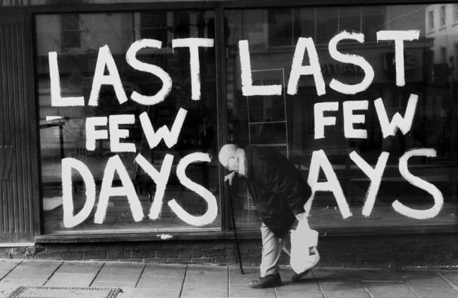 """Ein gebeugt gehender alter Mann vor einem Schaufenster mit der Aufschrift """"Last few days""""."""