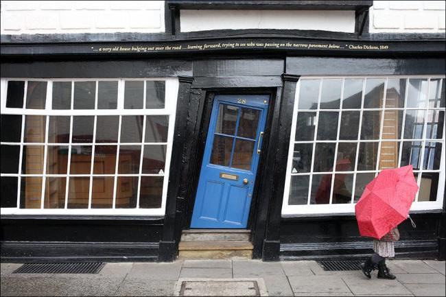 Eine Person mit rotem Regenschirm vor einer schiefen Fassade mit blauer Tür.