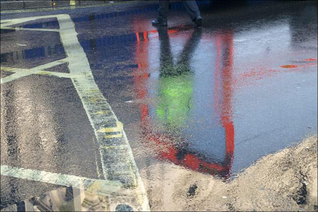Bunte Spiegelungen auf nassem Asphalt.