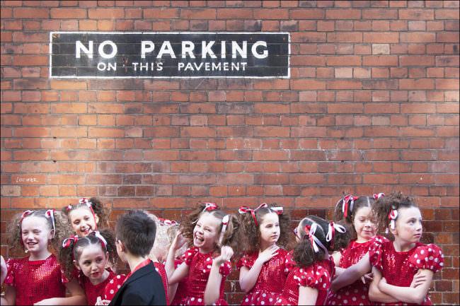 """Viele Mädchen in roten Kleidern und ein Junge im Anzug vor einer Backsteinmauer mit der Aufschrift """"No parking on this pavement""""."""