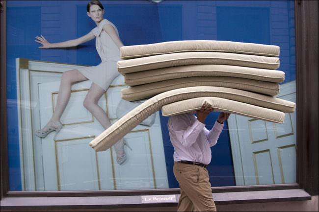 Ein Mann trägt einen Stapel Matrazen vor einem Bild einer Frau, die auf einer Tür sitzt.