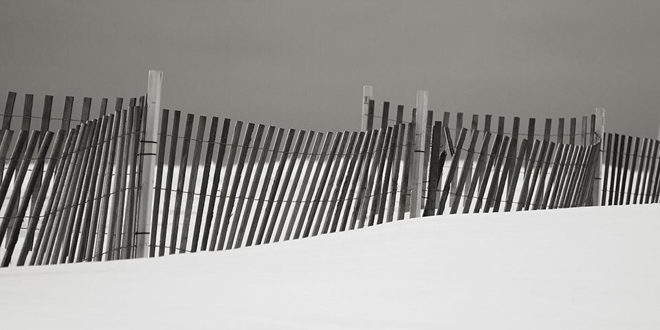 Ein Lattenzaun zwischen Schnee und grauem Himmel.