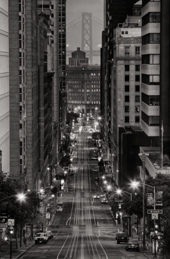Blick durch eine Straßenschlucht in einer nächtlichen Stadt.