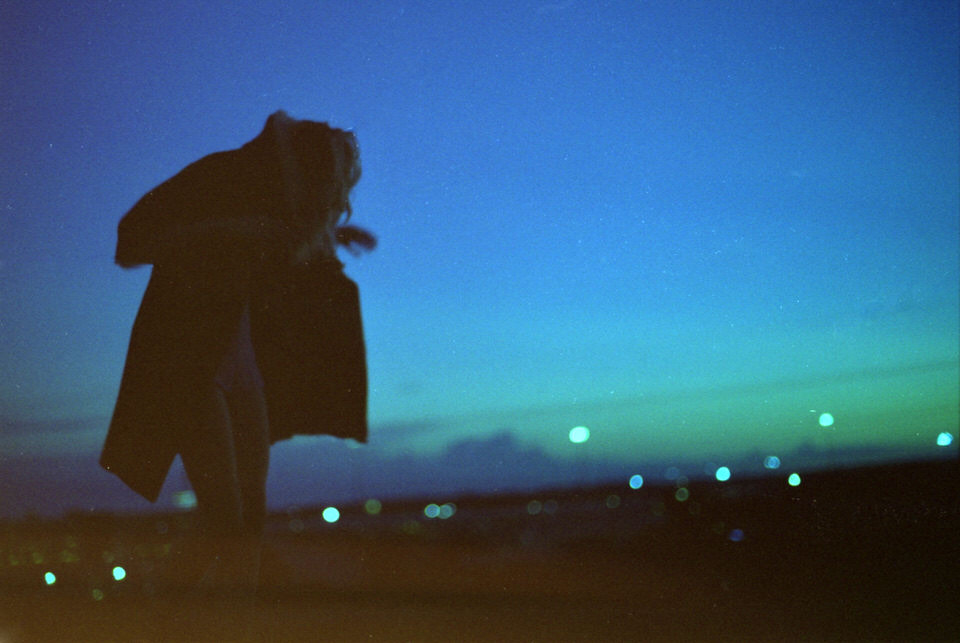 Person mit Mantel in der Nacht vor Lichtern in der Ferne.