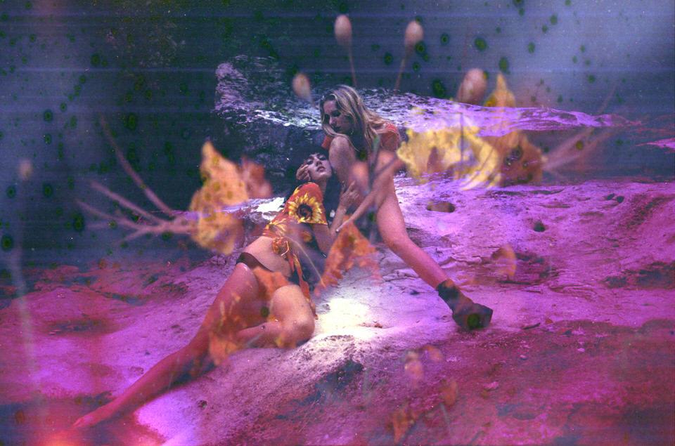 Doppelbelichtung: Zwei Frauen auf einem Felsen und Blumen.