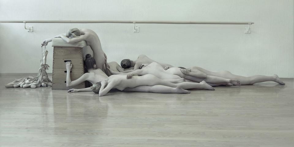 Einige nackte Menschen liegen in einer Turnhalle.