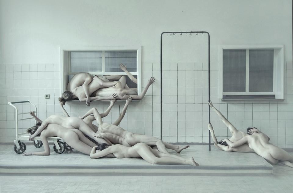 Einige nackte Menschen liegen in einem Krankenhausflur.