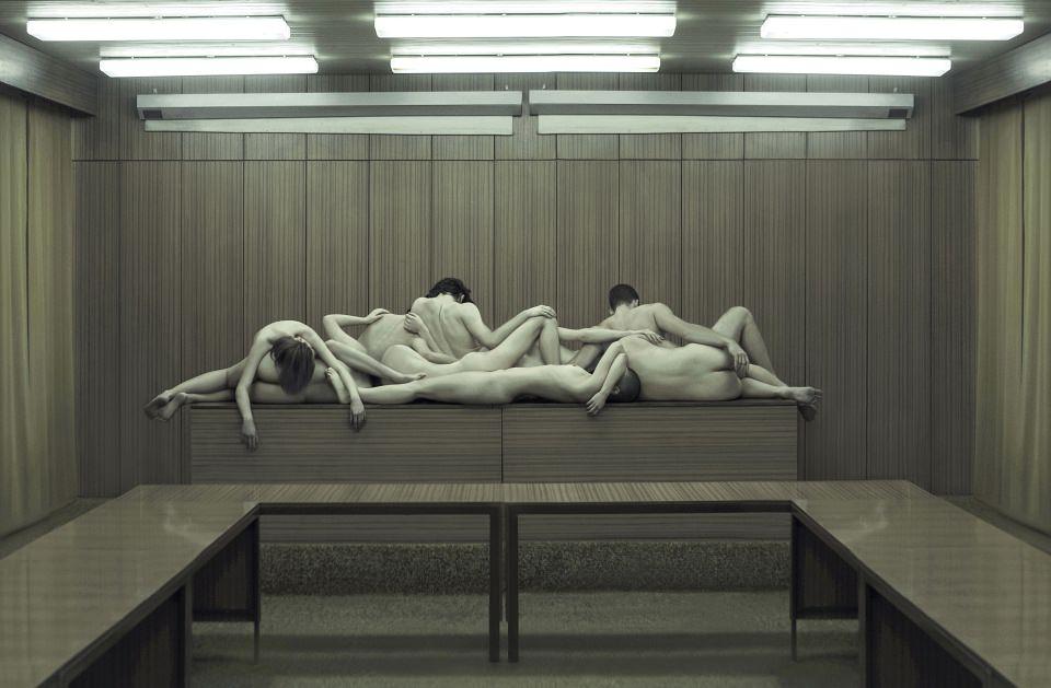 Einige nackte Menschen liegen auf einem Podium in einem Verwaltungssaal.