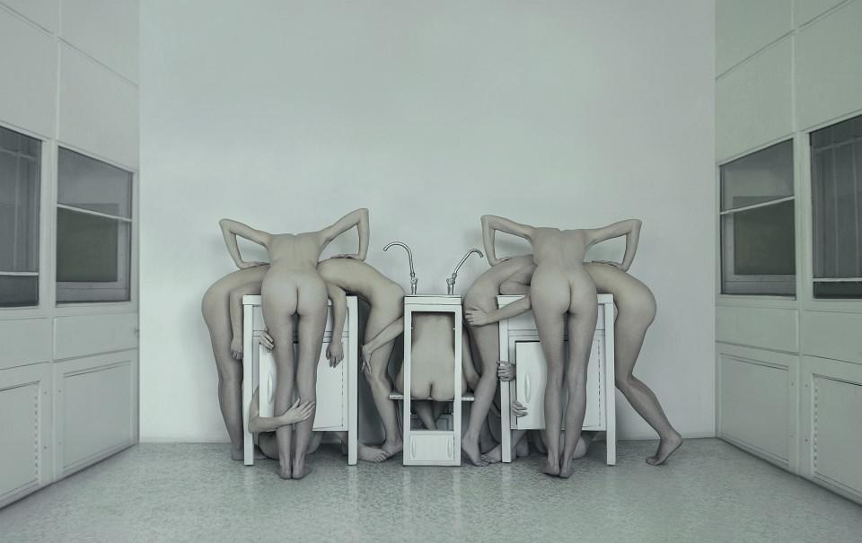 Einige nackte Menschen symmetrisch angeordnet in einem Waschzimmer.