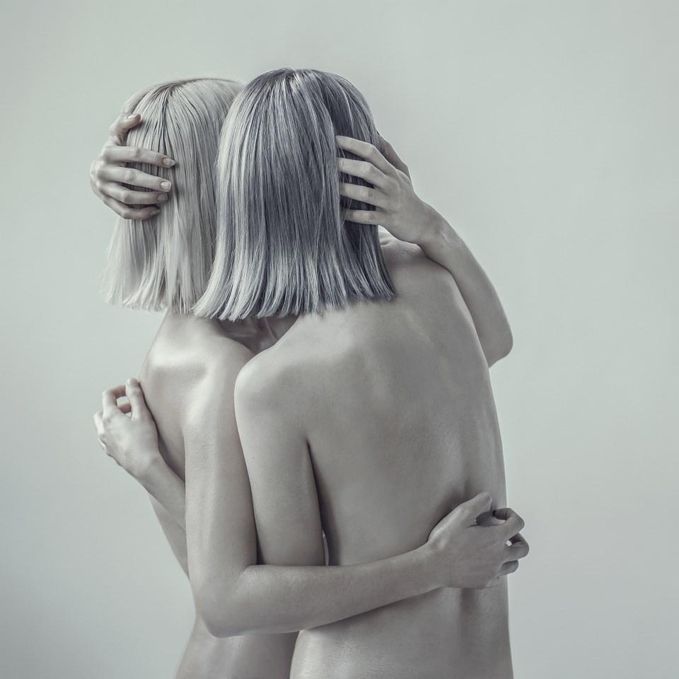 Rückansicht zweier nackter Frauen, die sich umarmen.