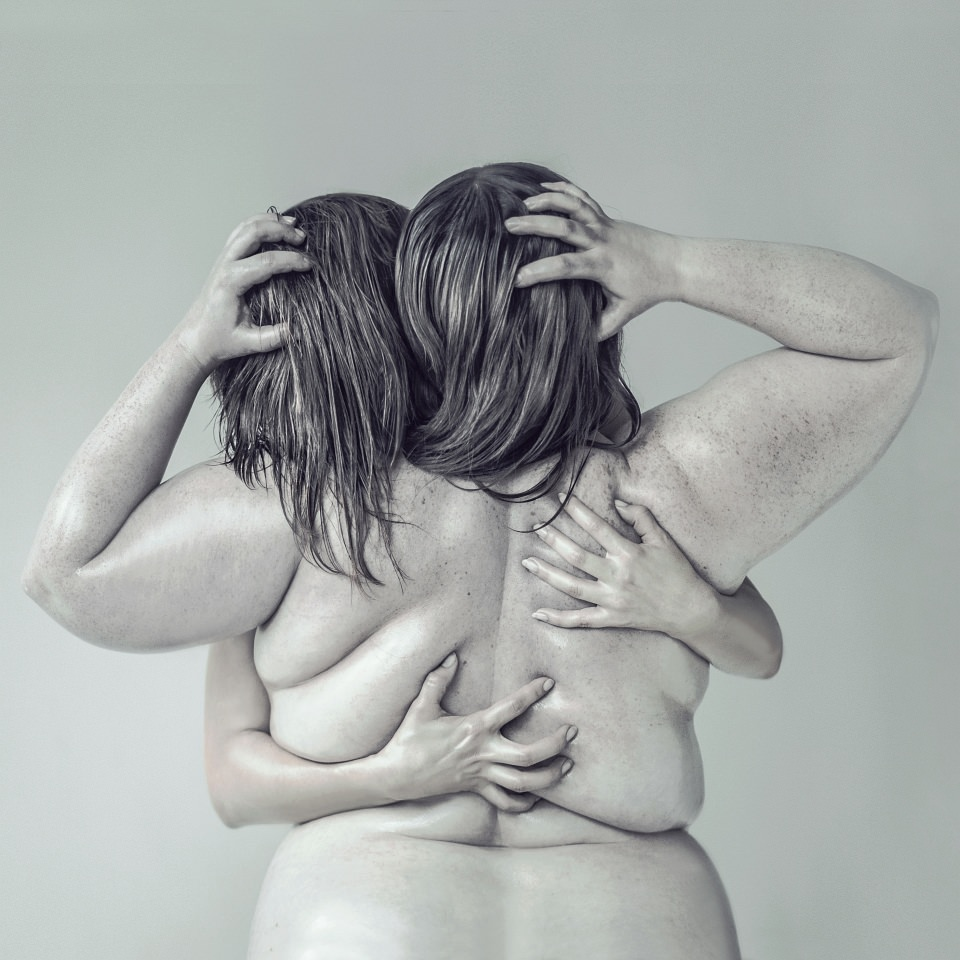 Eine beleibte, nackte Frau von hinten, die von einer weiteren Person umarmt wird.