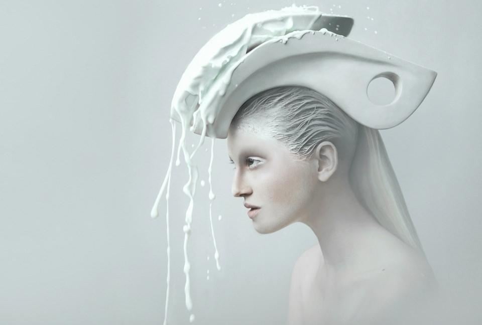 Portrait einer Frau mit weißer Skulptur auf dem Kopf, aus der weiße Flüssigkeit fließt.